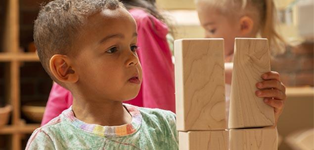 A boy stacking blocks.